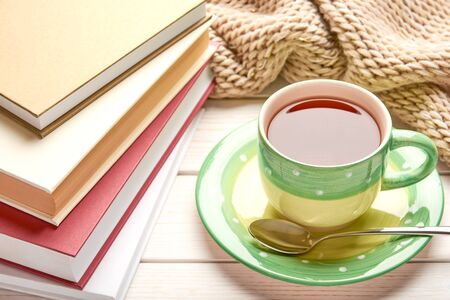 Still life on white wooden table top. Green cup of tea, spoon and stack of book in hard cover. Space for your text. Reklamní fotografie