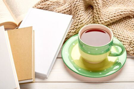 Still life on white wooden table top. Green cup of tea and stack of book in hard cover. Space for your text.