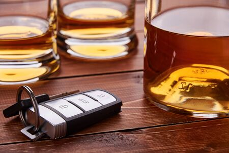 Still life with car keys and glass or bottles of whiskey. Wooden table top. Suitable for drunk driving. Reklamní fotografie