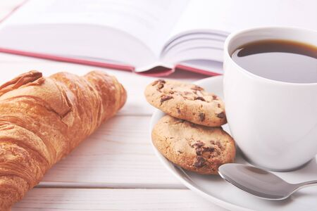 Still life with red book, cup of coffee or tea and two cookies. Croissant on white table top. Bright photo of breakfast. Reklamní fotografie