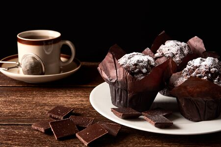 Still life with cup of tea or coffee and three chocolate muffins sprinkled with sugar. White plate on dark table top. Space for your text, black background.