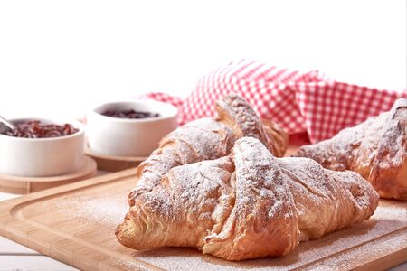 Still life with sugared croissants, fruit jam and red dish on wooden table top. Isolated on white background. Reklamní fotografie