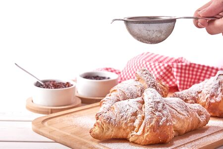 Still life with croissant and bowls of jam. Female hand holding a strainer and sprinkles sugar. Isolated on white background.