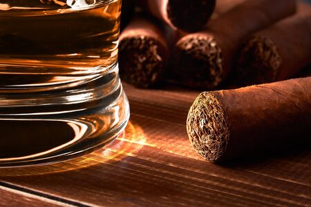 Still life with glass of whiskey or rum, cigar on old wooden board table. Blurred background. Reklamní fotografie
