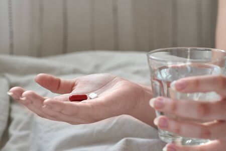 Close-up view of young woman's hands. Girl in bed holding tablets or pills and glass of water. Painkiller with space for text. Blurred background.