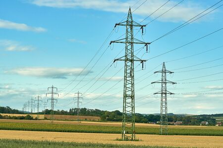 Agricultural landscape with blue sky and a row of high voltage pylons. Fields in South Moravia in the Czech Republic.