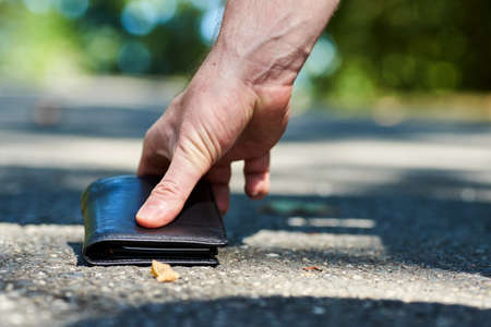 Photo of a sidewalk and the hand of a man who found a black leather wallet while walking