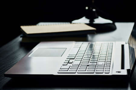 Side view of a silver laptop keyboard and a stack of exercise books in backlight. Wooden table top and black background.