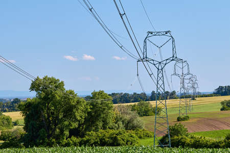 view of high power poles with electric wires in agricultural landscape in South Moravia, Czech Republic under summer blue sky Banque d'images