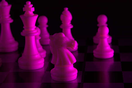 White chess pieces in a purple light with black background Banque d'images