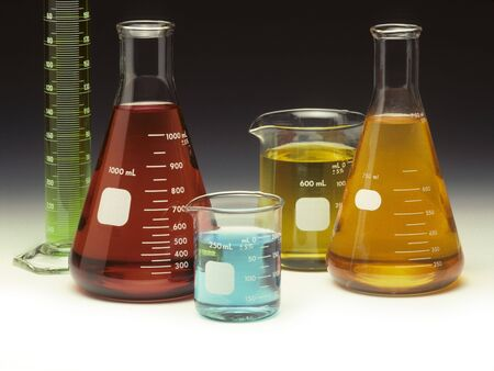 Scientific glassware filled with colored liquids on a graduated background
