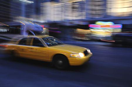 hustle: Taxicab correre gi� una strada di notte in una sfocatura cittadina Archivio Fotografico