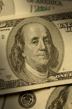 dramatically: Close-up of Benjamin Franklin on the $100 bill, dramatically lit.