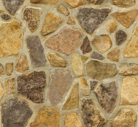 Seamless masonry wall with irregular shaped stones. The texture repeats seamlessly both vertically and horizontally. Stock Photo