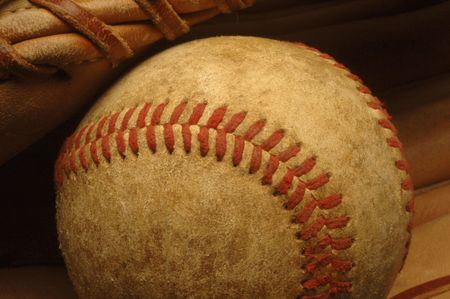 ballgame: A close-up of a well-worn baseball nestled in a glove.