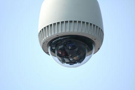 Overhead video security camera against a blue sky