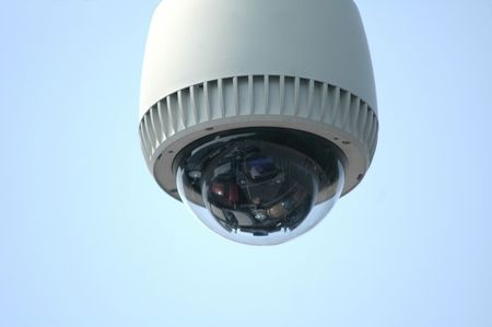 Overhead video security camera against a blue sky