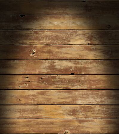 Distressed wooden surface lit dramatically from above with boards running horizontally.