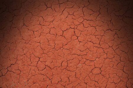 Cracked red textured surface background, dramatically lit from above photo