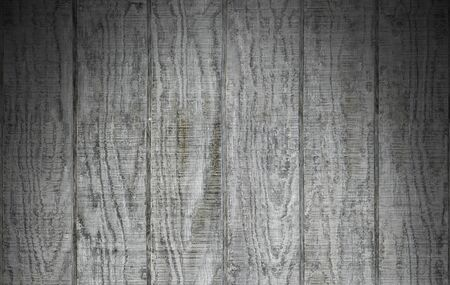 dramatically: Weathered gray wooden barn siding using vertical planks lit dramatically from above