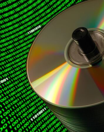 バイナリ コードの湾曲とダッチ アングル上の CD/DVD ディスクのスタックをクローズ アップ 写真素材 - 8991948