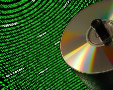 バイナリ コードの湾曲とダッチ アングル上の CDDVD ディスクのスタックをクローズ アップ 写真素材