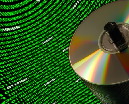 dvds: Close-up of a stack of CDDVD disks on a Dutch angle, with a curved field of binary code