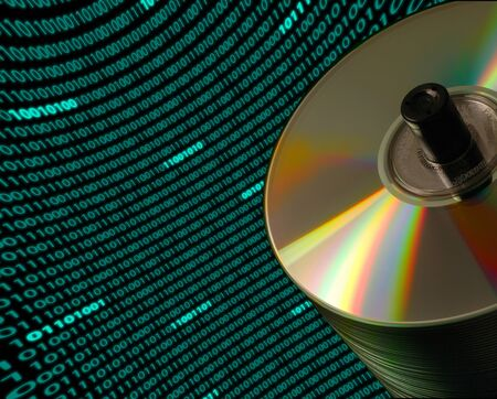 Close-up of a stack of CDDVD disks on an angle, with a curved field of binary code in the background photo