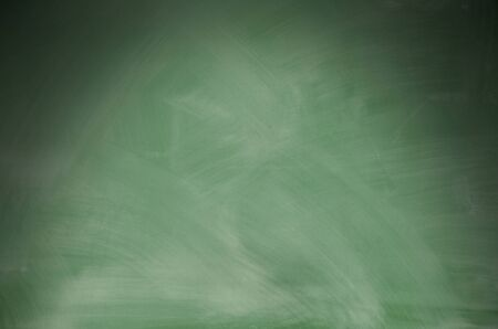 dramatically: Green chalkboard with eraser marks lit dramatically from above