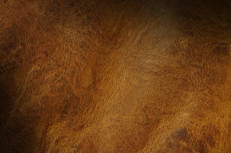 Distressed brown leather texture background lit diagonally photo