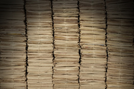 pile reuse: Five uniform piles of newspapers to be recycled lit from above Stock Photo