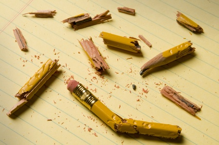 Shattered pencil fragments on a yellow legal pad, perhaps symbolizing writers block Stock Photo