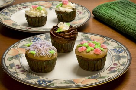 ornately: Close-up of ornately decorated cupcakes on plates