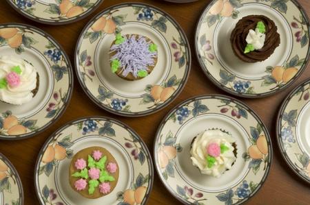 ornately: Close-up of ornately decorated cupcakes on plates
