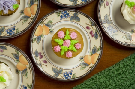 ornately: Close-up of ornately decorated cupcakes on dishes