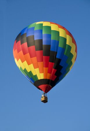 aloft: Colorful hot-air balloon floating against blue sky