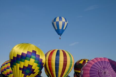 inflating: Hot-air balloon ascending over other inflating ones on the ground