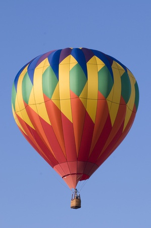 Colorful hot-air balloon floating against blue sky photo
