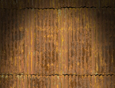 Corroded and rusty corrugated metal roof panels lit dramatically