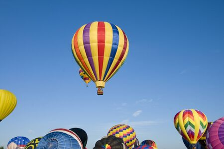aloft: Hot-air balloons ascending over inflating ones on the ground