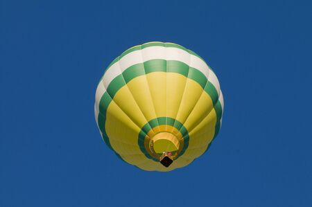 Green, white and yellow hot-air balloon airborne, shot from beneath Stock Photo - 11353824