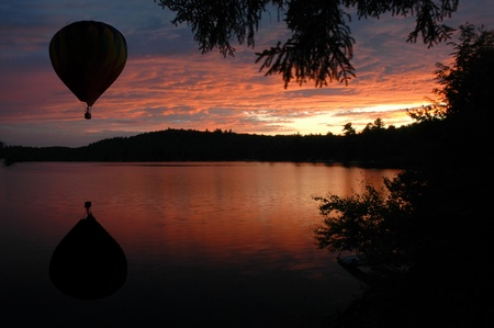 hot air: Hot-Air Balloon over Lake at Sunset Sunrise Stock Photo