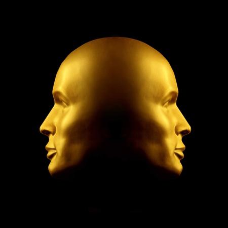Two faced gold head statue against black Standard-Bild