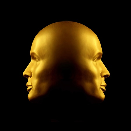deceit: Two faced gold head statue against black Stock Photo