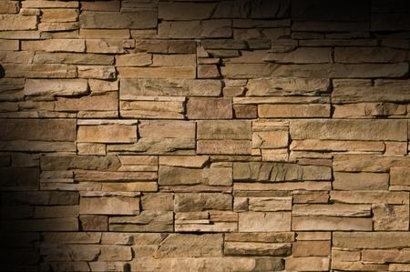 Irregular sized brown bricks with an organic feel, lit diagonally