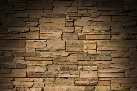 Irregular sized brown bricks with an organic feel, lit dramtically from above 版權商用圖片