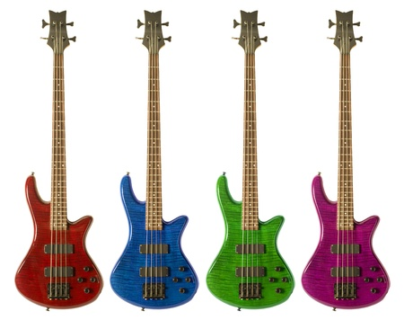 Multi-colored bass guitars against white background