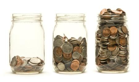 pote: Un número creciente de monedas americanas en unos tres tarros de cristal sobre un fondo blanco