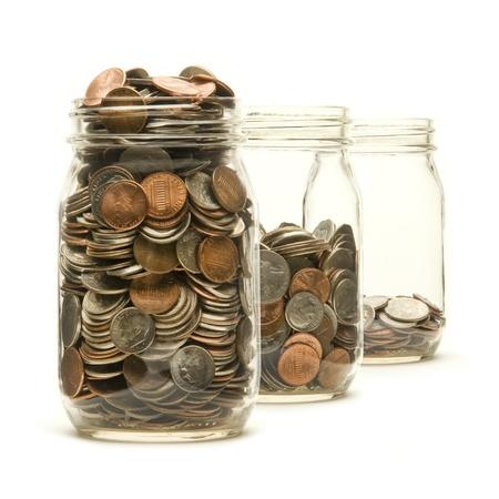 d�bord�: Trois bocaux en verre remplis de pi�ces de monnaie am�ricaines � des niveaux diff�rents sur un fond blanc Banque d'images