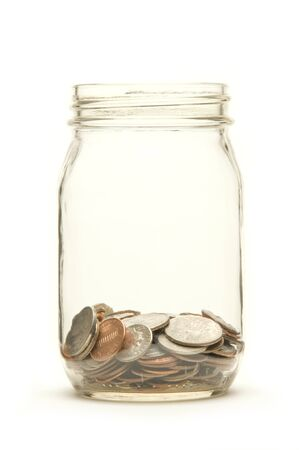penny pinching: American coins in a glass jar against a white background